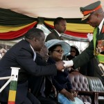 General Phillip Sibanda of the Army shakes Prime Minister Morgan Tsvangirai's hand during Defence Forces Day ceremonies in 2009 at a Harare stadium. Air Marshal Perance Shiri can be seen behind the General saluting General Mujuru.