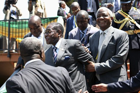 Unsteady Mugabe being helped by aides