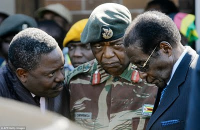 The head of the CIO Happyton Bonyongwe (left), army chief Constantine Chiwenga (centre) in discussion with Robert Mugabe.