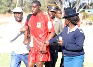 MARCHING ORDERS . . . Furious Motor Action striker Kudakwashe Musharu protests his expulsion as he is escorted off the pitch by assistant coach David George and police details at Motor Action Sports Club yesterday. [Picture by Kudakwashe Hunda