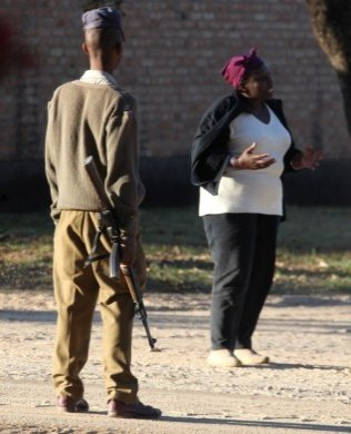 CLOSELY GUARDED... An armed police officer keeps a close eye on deputy Minster of Labour, Tracy Mutinhiri, at her Marondera farm, which a group of Zanu PF members tried to take over on Saturday. (Pic: Tsvangirayi Mukwazhi)