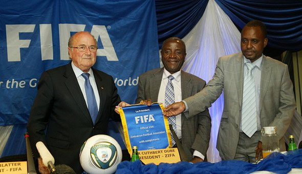 Sepp Blatter the FIFA President presents a commemorative plaque to the President of the Zimbabwe Football Association Cuthbert Dube (C) as the ZIFA Chief Executive Officer Jonathan Mashingaidze (R) watches in Harare on July 4, 2011. AFP PHOTO / JEKESAI NJIKIZANA