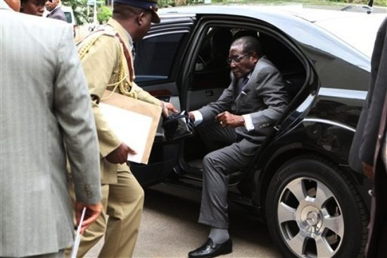 Hold this for me: The 87 year old Zanu PF leader stepped out of his armoured Mercedes limousine and handed the bag over to one of his bodyguards (picture by New Zimbabwe.com)