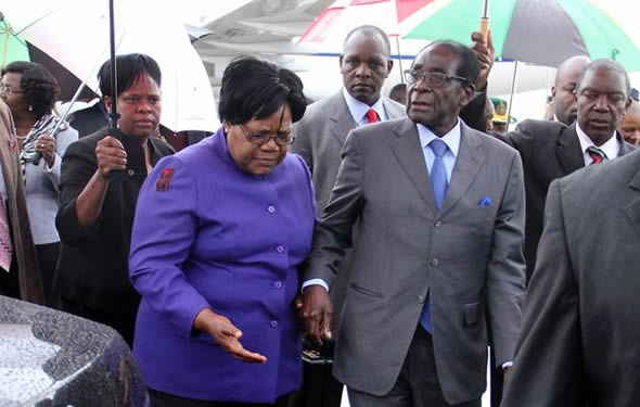 Zimbabwean President Robert Mugabe (R) is greeted by Vice President Joice Mujuru (L) as he returns home to Harare, April 12, 2012, after a trip to Singapore that had ignited speculation the veteran leader was seriously ill