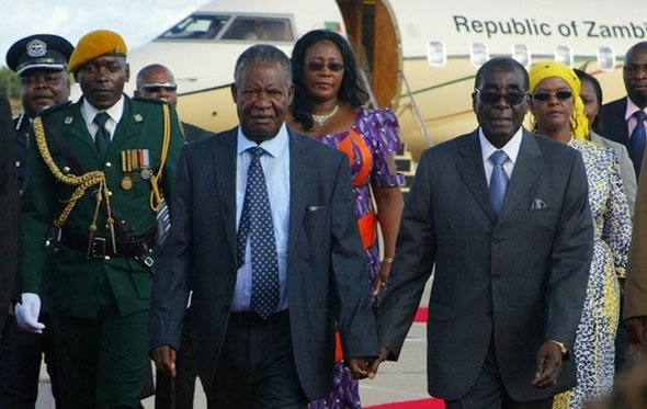 Zambian President Michael Sata is met by President Robert Mugabe. The first ladies are walking behind