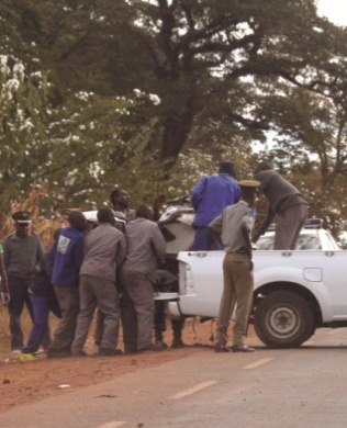 CLOSE SHAVE... Police officers lift a motorbike belonging to President Robert Mugabe's motorcade after it hit a pedestrian along Bulawayo Road in Kuwadzana in June this year. (Pic: Anne Mpalume-Daily News)