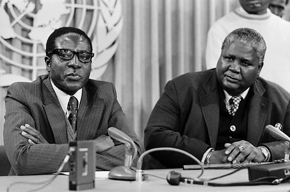Dictator Robert Mugabe (left) showing what his brutal regime really think about the late national hero Joshua Nkomo (right)