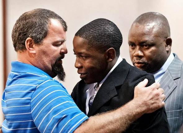 Tim See, left, hugs Takunda Mavima in the courtroom. See's son Timothy was a crash victim. At right is Mavima's father.