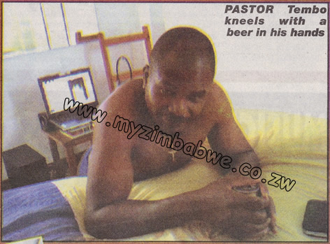 Pastor Tembo kneels in prayer with a beer in his hands