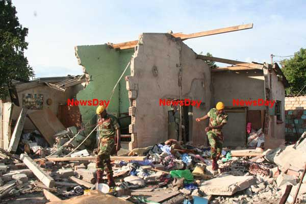 Soldiers inspect the damage after a house explosion killed 5 people in Zengeza.