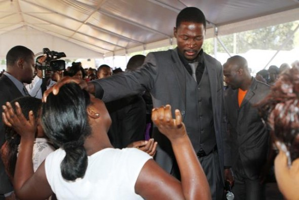 Prophet Emmanuel Makandiwa prays for members of his congregation