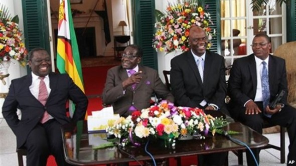 From left, Prime Minister Morgan Tsvangirai, President Robert Mugabe and other Zimbabwean officials address a press conference at the State House, Harare, Jan. 17, 2013