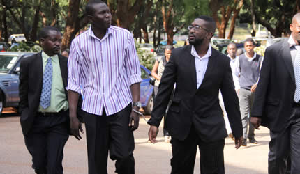 Dj Munya walks handcuffed to one of his alleged accomplices Mohammed Matare while flanked by two detectives