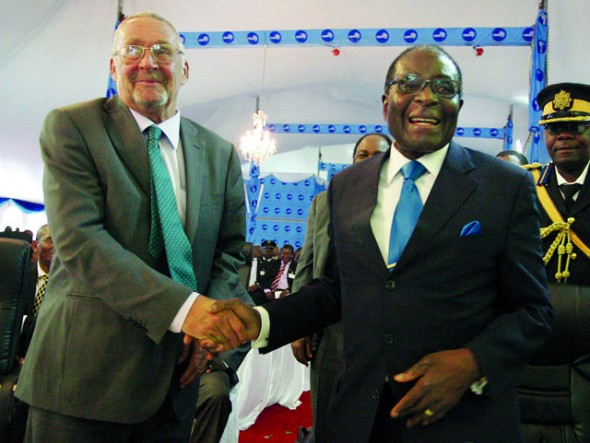 Zambia's Vice President Guy Scot (L) congratulates Zimbabwe's President Robert Mugabe on signing Common Market for Eastern and Southern Africa treaties (COMESA) during the 15th COMESA Summit in Lilongwe on October 14, 2011.