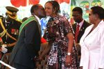 Zimbabwe's President Robert Mugabe (L) kisses his mistress turned wife Grace as he arrives to attend his country's 33rd independence celebrations at the National Sports stadium in Harare, April 18, 2013
