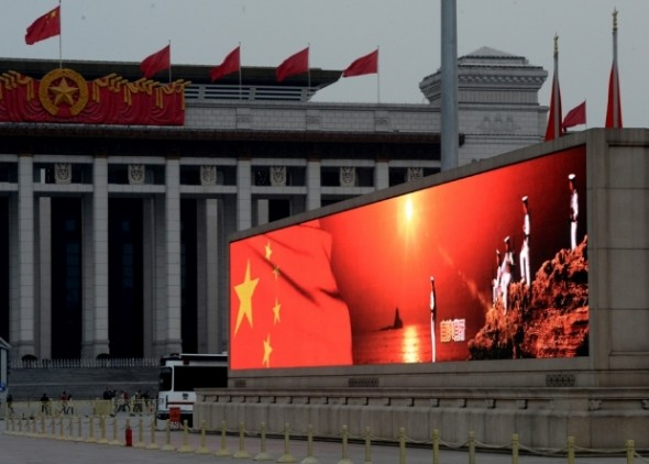 An image of the Chinese flag and sailors standing on the disputed Spratly Islands in the South China sea is displayed on a big screen in Tiananmen Square, March 2, 2013