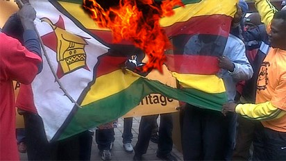 Protesting youths burning Zimbabwe flag
