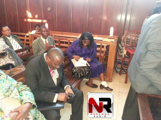 Dorothy Mabika retrieves her papers from her purse for submission while Manicaland Governor Chris Mushowe plays with his phone.