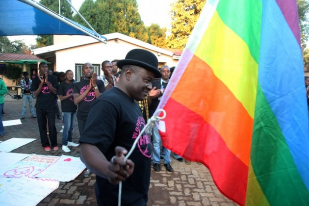 Director of the Gays and Lesbians Association of Zimbabwe, Chesterfield Samba prepares to hoist their official flag alongside the Zimbabwe flag
