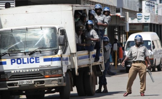 Zimbabwean riot police move in to quash a meeting organized by the Movement For Democratic Change, MDC, at their party headquarters in Harare Sunday April 3, 2011