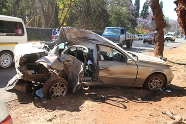 Two children died on the spot when this car was side-swiped and veered off the road before ramming a tree along Golden Stairs Road in Emerald Hill yesterday morning. The driver was attacked by bees as he crawled out of the wreckage. — (Picture by Innocent Makawa)