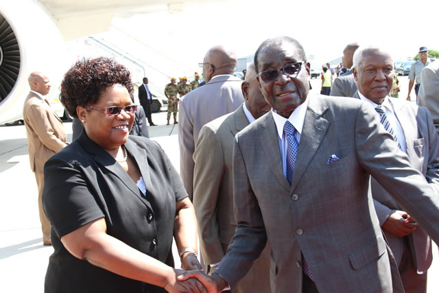 President Mugabe chats to VP Mujuru at the Harare International Airport before his departure