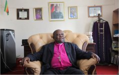 Bishop from Hell: Nolbert Kunonga in his Harare offices with a picture of Robert Mugabe in the background