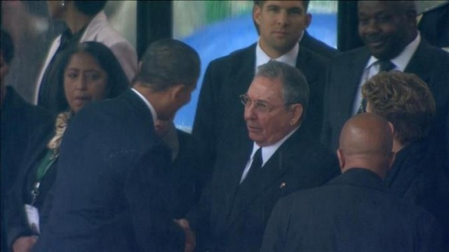 U.S. President Barack Obama (2nd L) shakes hands with Cuban President Raul Castro (C) in this still image taken from video courtesy of the South Africa Broadcasting Corporation (SABC) at the First National Bank (FNB) Stadium, also known as Soccer City, during former South African President Nelson Mandela's national memorial service in Johannesburg December 10, 2013. Obama shook the hand of Castro at a memorial to Mandela on Tuesday, an unprecedented gesture between the leaders of two nations which have been at loggerheads for more than half a century.