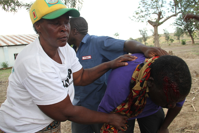 A Zanu-PF supporter is assisted by colleagues as blood flows from a gash on his head in Mhangura. Police had to fire tear gas to quell violent skirmishes that arose out of factional loyalties and the non-appearance of some names on the voters' roll during weekend provincial polls.