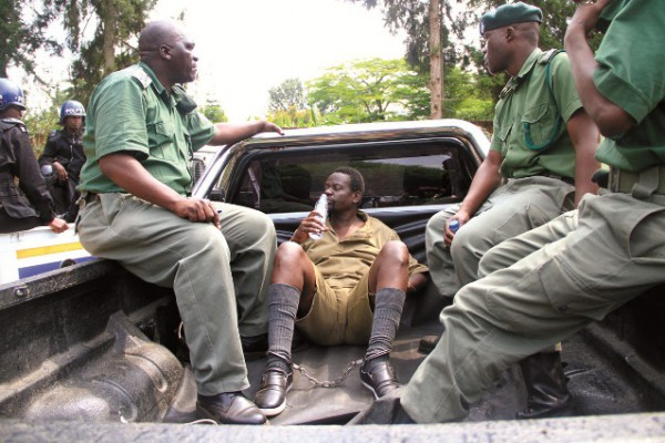 CHAINED...Gumbura, who is facing multiple rape charges, is escorted by prison guards for an inspection-in-loco at his home.