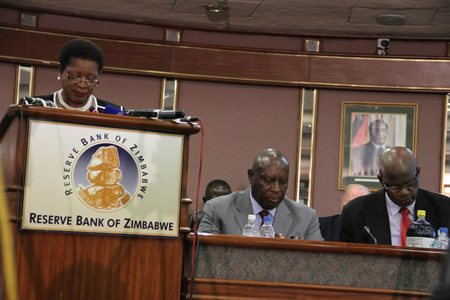 RBZ Acting Governor Charity Dhliwayo presents the monetary policy, while Minister of Finance and Economic Development Patrick Chinamasa and his Deputy Samuel Udenge follow the proceedings at RBZ Building in Harare