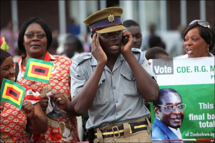 A Zimbabwean police officer talks on his phone beside a supporters and a portrait of Robert Mugabe