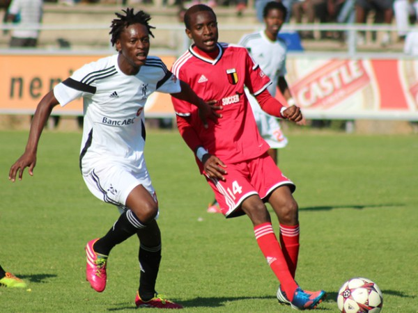 Highlanders FC striker Charles Sibanda (left) chases the ball closely ...