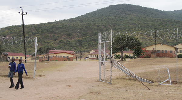 Two students walk past a gate damaged during the violent protests at Mutambara High School this week