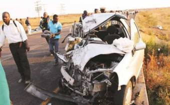 Police and onlookers at the scene of the crash along the Plumtree-Bulawayo highway yesterday