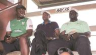 POACHED? . . . Former Highlanders coach Kelvin Kaindu (centre) watches yesterday's Premiership soccer match between Triangle and CAPS United at Gibbo in the company of Triangle team manager Cherechedzai Murare (right) and an unidentified Triangle fan