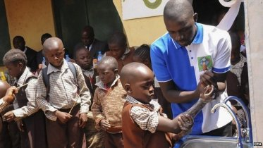 Schoolchildren in Nigeria wash their hands as they learn about Ebola prevention
