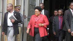 Joice Mujuru leaves the Magistrates Court during the inquest into her husband's death. General Mujuru died in a suspicious fire two years ago.