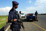 A heavily-armed policeman keeps a lookout while  Ethiopian nationals wait next to a bakkie loaded with goods while fleeing their shop in Meadowlands, Soweto during violent looting of foreign-owned shops in the area, Thursday, 22 January 2015. Two people have been shot dead and two injured since violence broke out between locals and foreigners. Foreign-owned shops have been looted. The looting started on Monday after 14-year-old Mthetheleli Siphiwe Mahori was shot dead, allegedly by a foreign shop owner in Snake Park. He was apparently part of a group that tried to rob the shop. Many foreigners had left the area for their own safety. Picture: Werner Beukes/SAPA