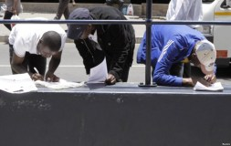 FILE - Zimbabweans fill out application forms outside Immigration offices in Johannesburg.