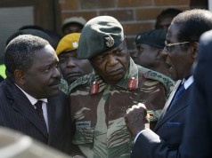 The head of Zimbabwe Central Intelligence Organisation (CIO) Happyton Bonyongwe (L) with Constantine Chiwenga, the commander of the Zimbabwean Army (C) listen to President Robert Mugabe at Harare Airport, on July 03, 2008.