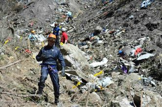 Chilling Scene: French investigators make their way through debris from wreckage on the mountainside at the crash site of an Airbus A320
