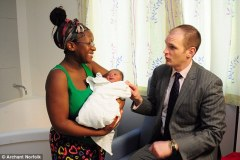New mother: Zimbabwe-born Caroline Nyadzayo (left) was pictured with health minister Daniel Poulter (right) on his visit to the Norfolk and Norwich University Hospital in the maternity suite