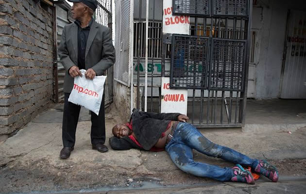 Mozambique national Emmanuel Sithole collapses on the pavement after he was attacked by men in Alexandra township in Johannesburg on April 18, 2015. He later died from his wounds. Image by: JAMES OATWAY Sunday Times.