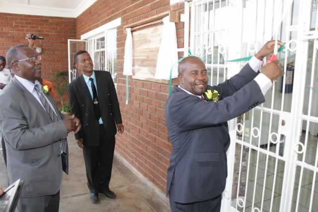 File Picture: Permanent Secretary in the Ministry of Higher and Tertiary Education, Science and Techology Development Dr Washington Mbizvo cuts the ribbon to officially open Padandaro Lodge in Mutare, while Mutare Poly principal Mr Tobias Kuwengwa (left) and a college staffer look on