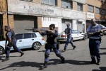 Police officers fire rubber bullets as they disperse African immigrants carrying machetes (Siphiwe Sibeko/Reuters)
