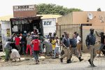 BLIND EYE: Police officers stroll away from a crowd looting a shop in White City, Soweto