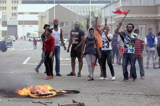 Foreign nationals gesture after clashes broke out between a group of locals and police in Durban on April 14 ,2015. (Photo by AFP)