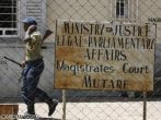 A Zimbabwean policeman patrols outside the entrance of Mutare Magistrates court.