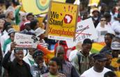 Demonstrators carry placards during a march against xenophobia in downtown Johannesburg, April 23, 2015. REUTERS/MIKE HUTCHINGS